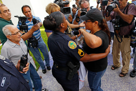 MIAMI, FL - APRIL 10:  An Ozzie Guillen supporter is confronted during a rally outside a press conference held by Miami Marlins Manager Ozzie Guillen for comments made about Fidel Castro at Marlins Park on April 10, 2012 in Miami, Florida. The Marlins suspended Guillen for five games over his pro-Castro comments.  (Photo by Mike Ehrmann/Getty Images)
