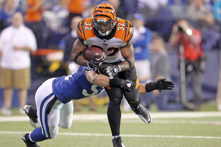 INDIANAPOLIS - NOVEMBER 14:  Cedric Benson #32 of the Cincinnati Bengals runs with the ball while defended by Phillip Wheeler #50 of the Indianapolis Colts during the NFL game at Lucas Oil Stadium on November 14 2010 in Indianapolis Indiana.  (Photo by Andy Lyons/Getty Images)