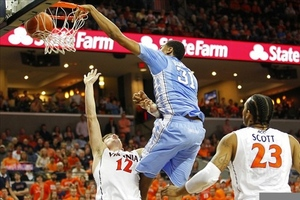 February 25, 2012; Charlottesville, VA USA; North Carolina Tar Heels forward John Henson (31) dunks the ball over Virginia Cavaliers guard Joe Harris (12) in the second half at John Paul Jones Arena. The Tar Heels won 54-51. Mandatory Credit: Geoff Burke-US PRESSWIRE