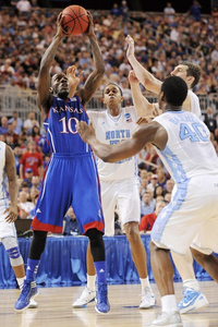 Mar 25, 2012; St. Louis, MO, USA; Kansas Jayhawks guard Tyshawn Taylor (10) shoots as North Carolina Tar Heels forward Harrison Barnes (40), forward Tyler Zeller (right) and forward John Henson (rear) defend during the second half of the finals of the midwest region of the 2012 NCAA men's basketball tournament at the Edward Jones Dome. Kansas won 80-67. Mandatory Credit: Jeff Curry-US PRESSWIRE