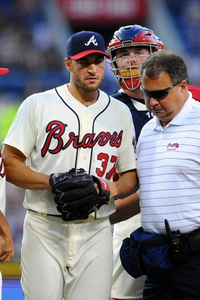 Brandon Beachy walks off the mound with the Braves trainer.